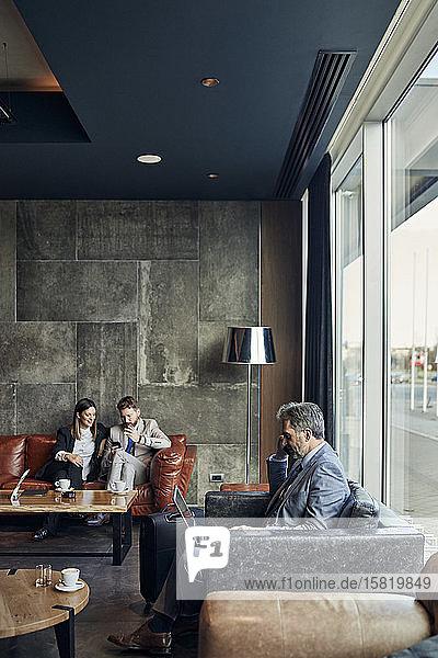 Geschäftsmann und Geschäftsfrau sitzen auf der Couch in der Hotellobby und teilen sich ein Smartphone