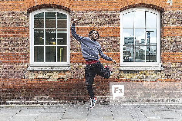 Junger Mann springt vor Ziegelmauer