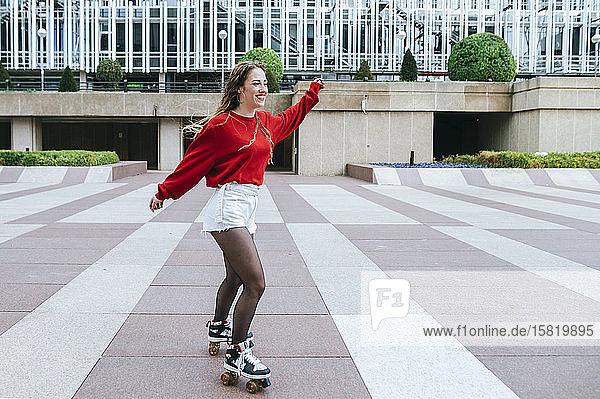 Glückliche junge Frau beim Rollschuhlaufen in der Stadt