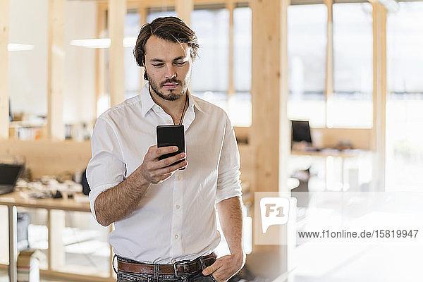 Geschäftsmann benutzt Handy im hölzernen Großraumbüro