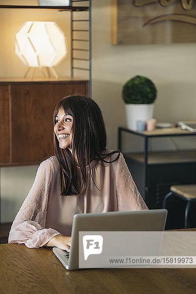 Lächelnde junge Frau benutzt Laptop zu Hause