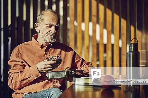 Entspannter Geschäftsmann beim nachhaltigen Mittagessen in seinem Büro