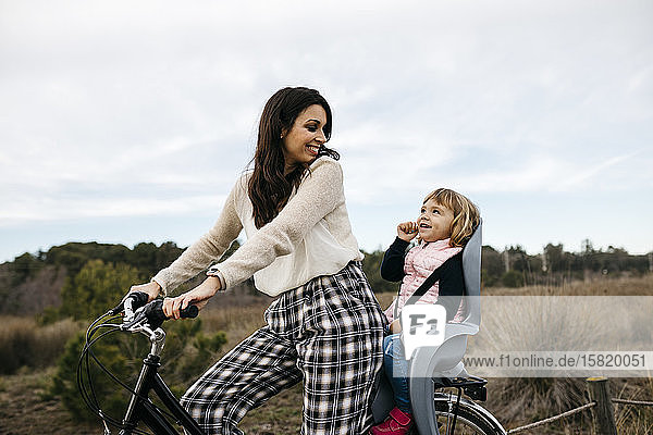 Woman riding bicycle in the countryside with daughter in child's seat