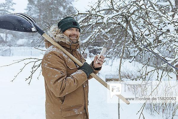 Porträt eines lächelnden Mannes mit Schneeschaufel und Mobiltelefon
