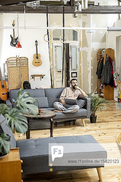 Junger Mann sitzt zu Hause auf dem Sofa und benutzt ein digitales Tablett