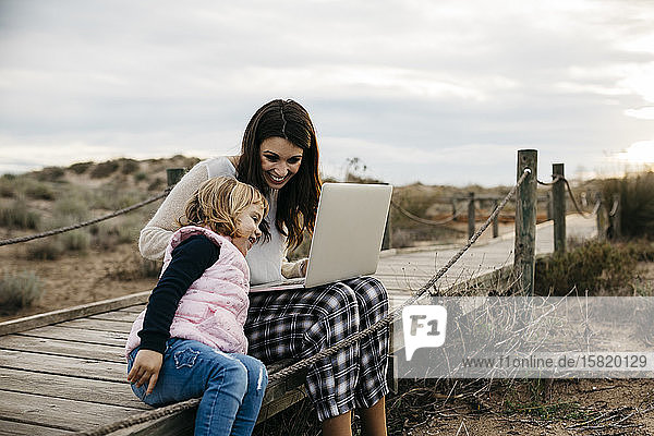 Mother with laptop and daughter on a boardwalk in the countryside