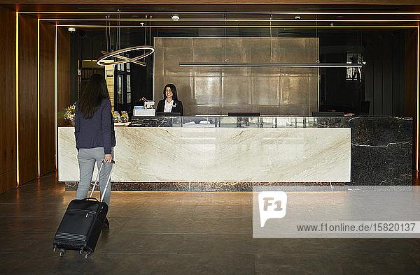 Businesswoman walking towards reception desk in hotel