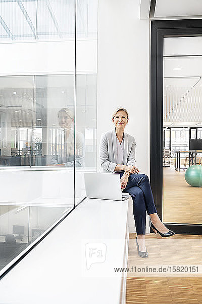 Blonde Geschäftsfrau mit Laptop  auf der Fensterbank eines Bürogebäudes sitzend