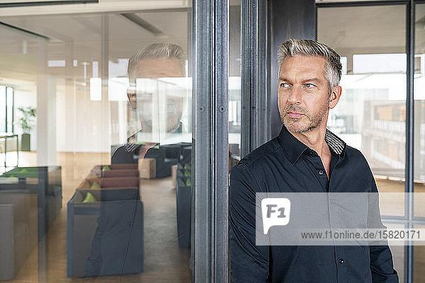 Buinessman im Büro stehend  an Glaswand gelehnt  nachdenkend