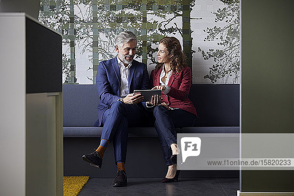 Businessman and businesswoman sitting on couch in office sharing tablet