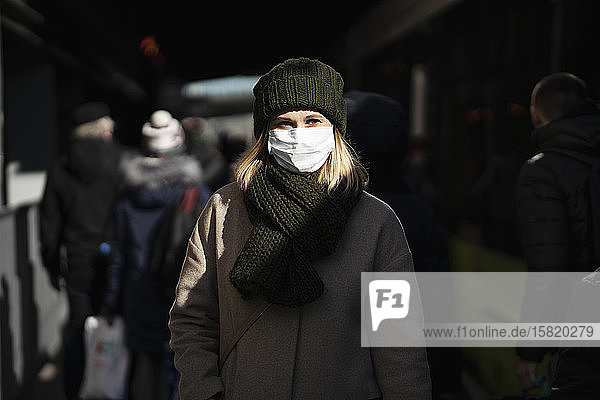 Woman with face mask standing at bus stop
