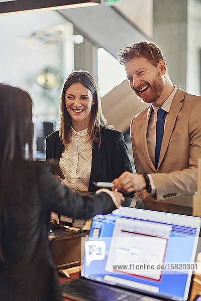 Business people paying at hotel reception