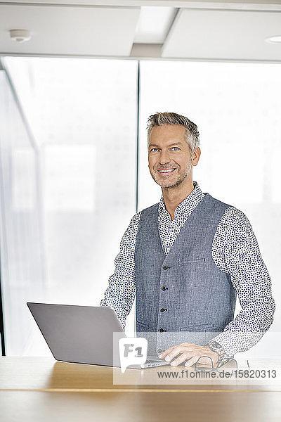 Porträt eines lächelnden Geschäftsmannes  mit Laptp