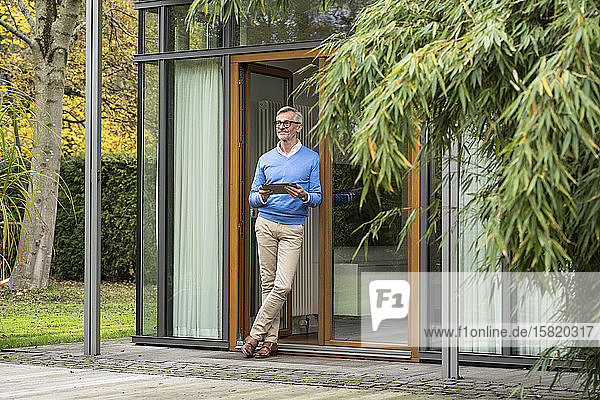 Senior man with grey hair standing in front of his modern design home holding tablet