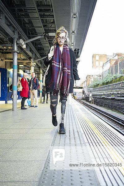 Junge Frau mit Beinprothese beim Gehen am Bahnsteig