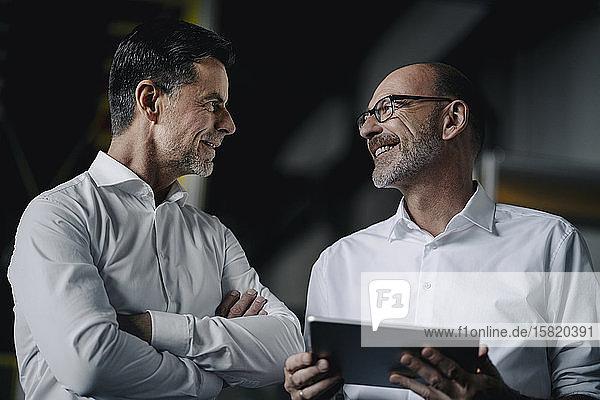 Zwei lächelnde Männer mit Tablette im Gespräch in einer Fabrik