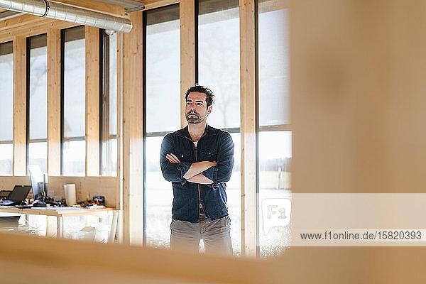 Geschäftsmann steht am Fenster in einem hölzernen Großraumbüro