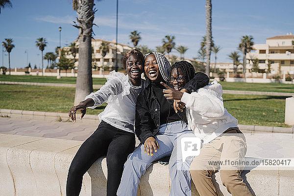 Glückliche Teenager-Freundinnen sitzen im Freien an einer Wand