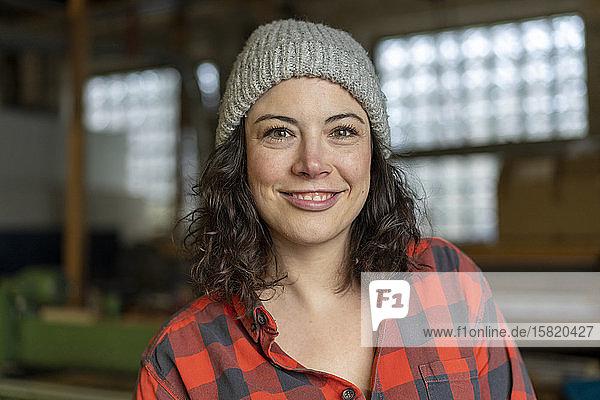Porträt einer selbstbewussten Handwerkerin in ihrer Werkstatt