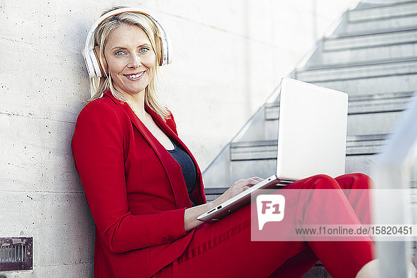 Blond businesswoman wearing red suit  sitting on stairs and using laptop