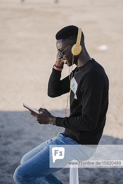 Stilvoller junger Mann  der im Freien mit Kopfhörern Musik hört