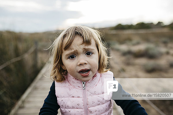 Portrait of a sad toddler girl on a boardwalk in the countryside