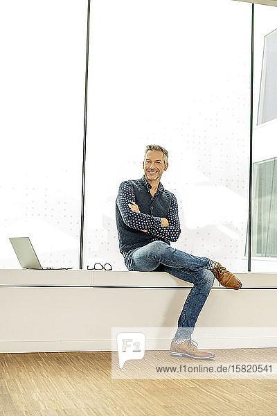 Gelegenheitskaufmann  der auf der Fensterbank eines Bürogebäudes sitzt  mit einem Laptop neben sich