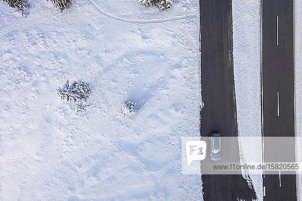Deutschland  Bayern  Luftaufnahme eines Autos  das im Winter auf einer Landstraße fährt