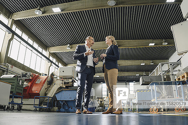 Geschäftsmann und Geschäftsfrau im Gespräch in einer Fabrik