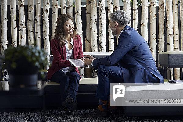 Geschäftsmann und Geschäftsfrau sitzen auf der Couch im Büro und teilen sich ein Tablet