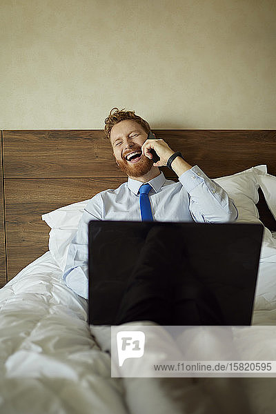 Businessman lying on bed in hotel room laughing on the phone