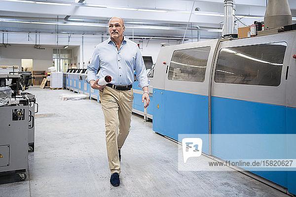 Geschäftsmann zu Fuß in einer Fabrik