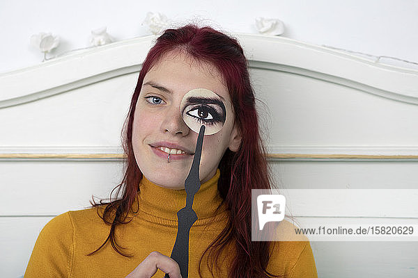 Portrait of redheaded woman with paper mask