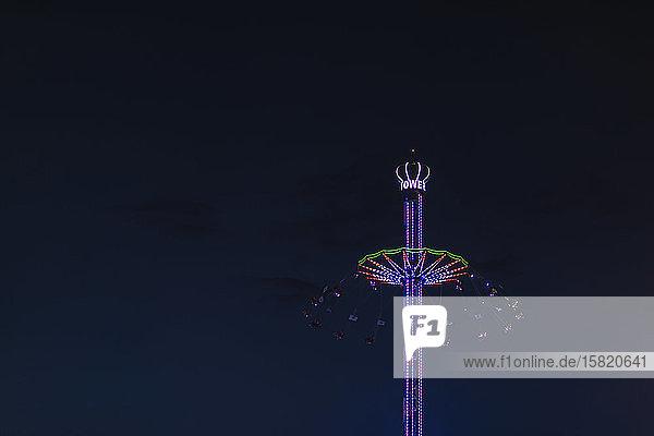 Deutschland  Bayern  München  Niederwinkelansicht der Kettenschaukel des Bayern-Turms  die nachts gegen den Himmel leuchtet
