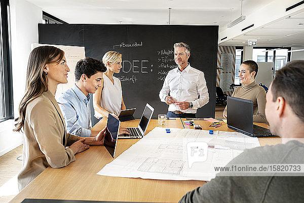 Geschäftsleute  die einen Workshop im Büro haben und Pläne besprechen