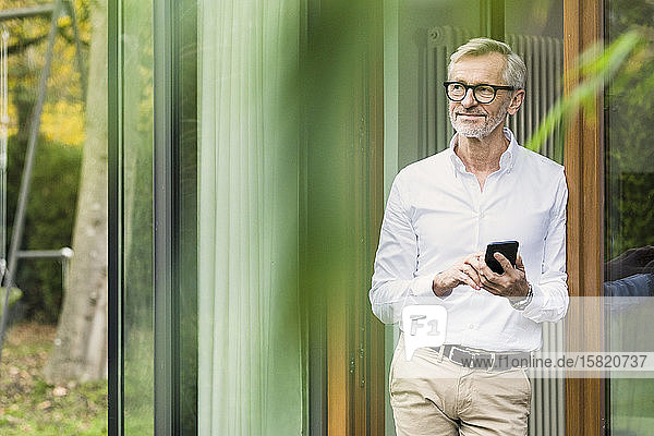 Smiling senior man with grey hair standing in front of his modern design home holding smartphone