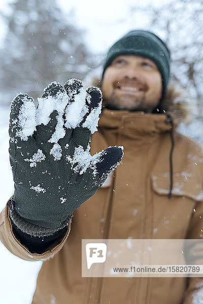 Man showing green glove with snow  close-up