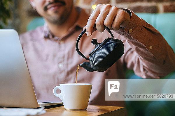 Mann mit Laptop in einem Café  der Tee in eine Tasse gießt