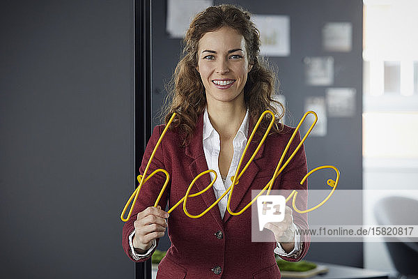 Portait of smiling businesswoman holding 'hello' neon sign in office