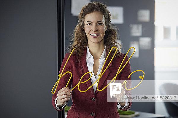Porträt einer lächelnden Geschäftsfrau mit einer Neonreklame Hallo im Büro