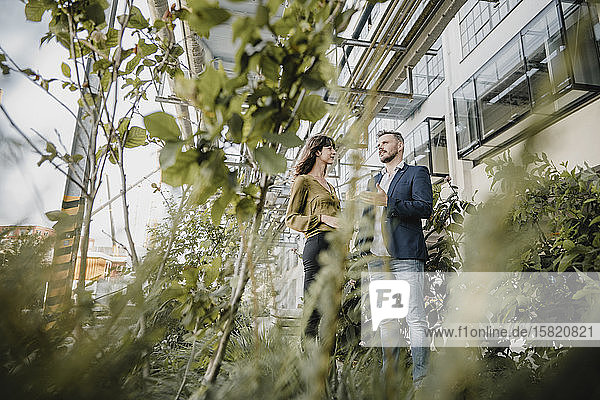 Geschäftsmann und zufällige Geschäftsfrau sprechen im Freien