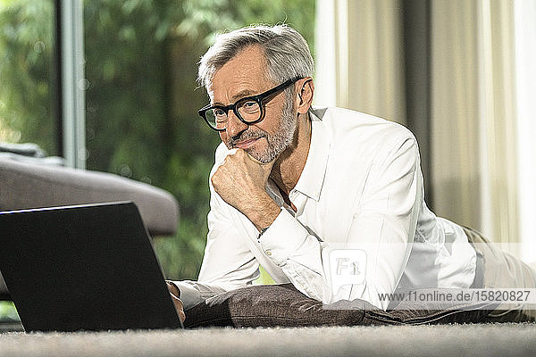 Smiling senior man with grey hair in modern design living room working on laptop