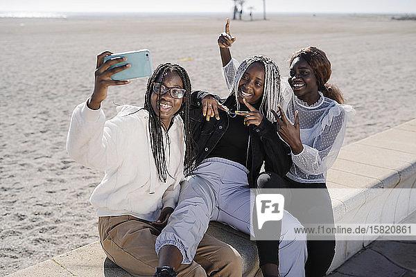 Porträt von glücklichen Teenager-Freundinnen  die am Strand ein Selfie machen