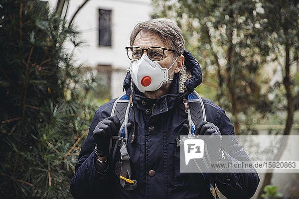 Matuer Mann,  der in der Stadt pendelt und eine Schutzmaske trägt