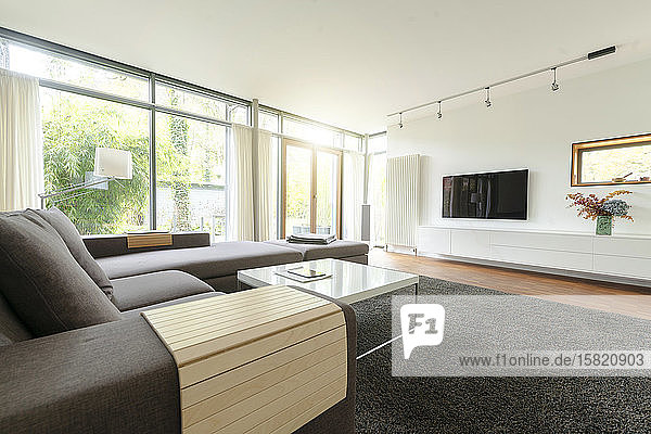 Modern living room in design house with large windows