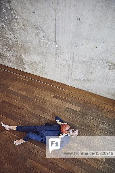 Leitender Geschäftsmann auf Holzboden liegend  mit Basketball spielend