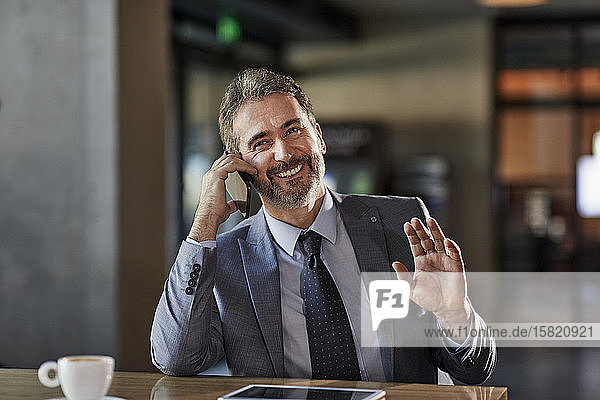 Portrait of a smiling businessman at table on the phone