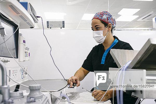 Frau kontrolliert Maschinen und Instrumente in einer Tierklinik