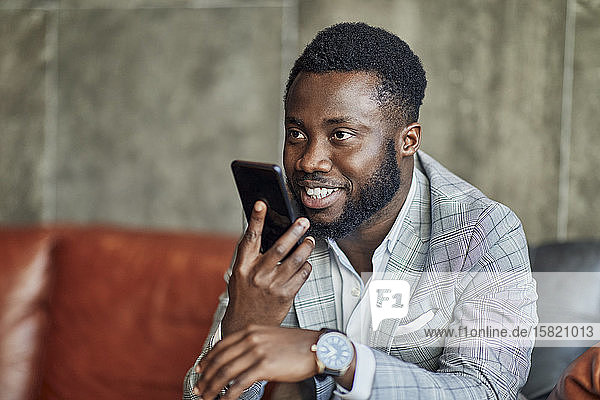 Businessman using smartphone in hotel lobby