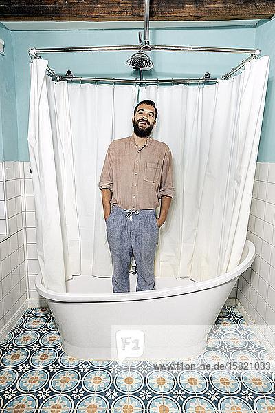 Junger Mann steht in der Badewanne und lacht